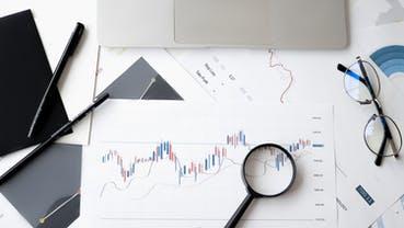 Ein Schreibtisch mit einem Graphen unter einer Lupe als Symbolbild für eine wikifolio Presseaussendung